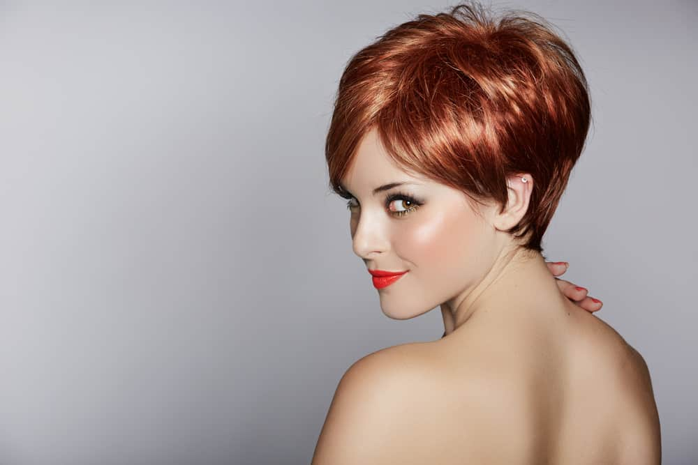 Woman with red hair in pixie style.