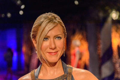 Jennifer Aniston with her long blonde hair pulled back to an upstyle hairstyle with side bangs at the Madame Tussauds museum in SF 2014.