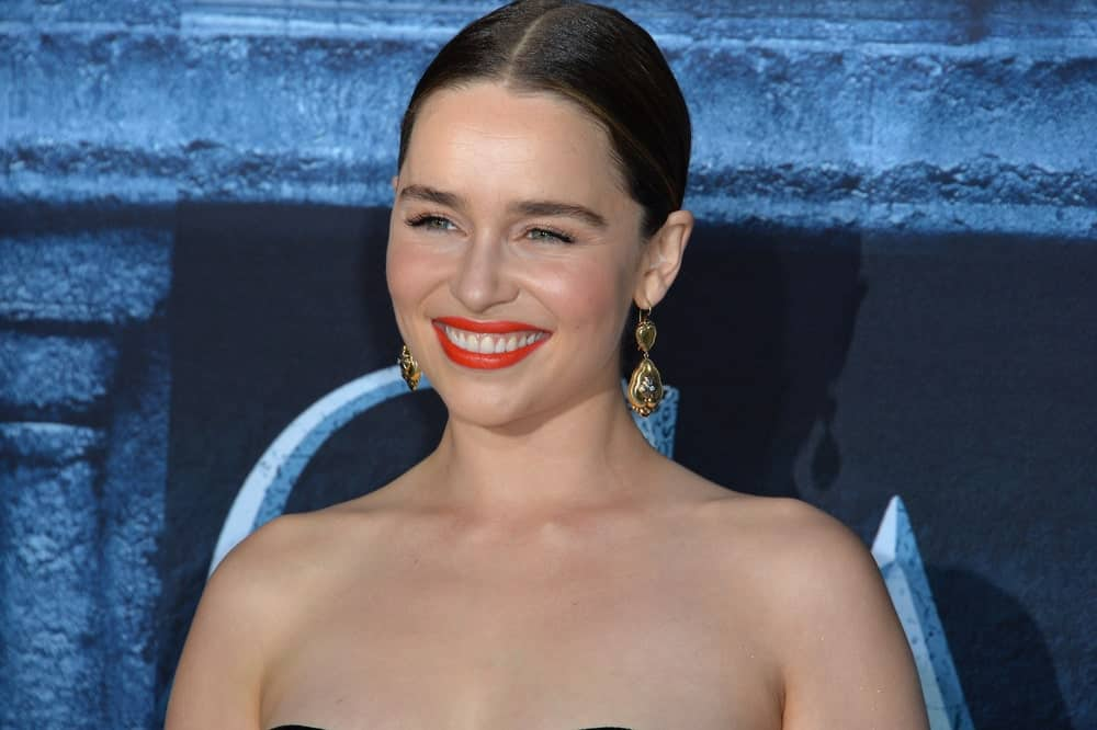 Actress Emilia Clarke with her tied waist-length hair style at the back at the season 6 premiere of Game of Thrones 2016. She is wearing a tube black dress accentuating her elegance and beauty.