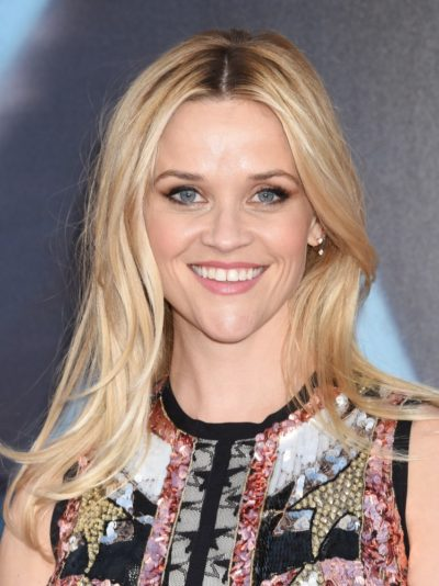 Reese Witherspoon with long blonde hair styled with center part in December 2016.