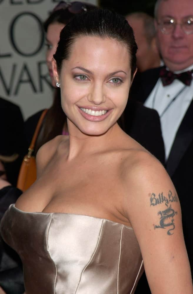 Actress Angelina Jolie was at the 2001 Golden Globe Awards at the Beverly Hilton Hotel. She came wearing a stunning silver strapless dress to match with her slicked raven bun hairstyle and brilliant smile.