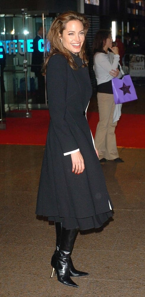 Angelina Jolie was all smiles in her lovely black dress and black boots at the UK premiere of 'Alexander' at the Odeon, Leicester Square on January 5, 2005. She paired this dress with her medium-length tousled loose hairstyle with a brown hue.