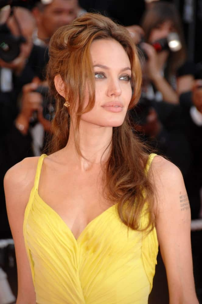 Angelina Jolie wowed everyone with her sexy yellow dress that went quite well with her loose and tousled half up hairstyle with bangs at world premiere for