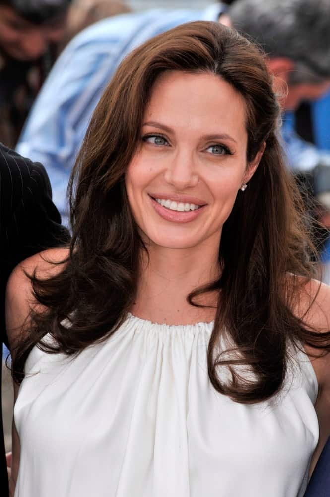 Angelina Jolie's iconic smile paired well with her simple white outfit and center-parted loose and tousled hairstyle with waves and layers at the photocall for her new movie