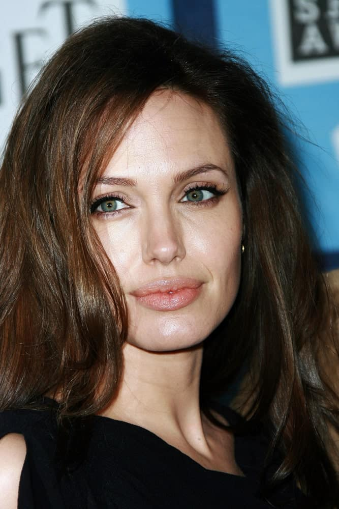Angelina Jolie's simple make-up and black dress paired well with her loose and tousled wavy hairstyle with long side-swept bangs at the 2008 Film Independent Spirit Awards at Santa Monica Beach, Santa Monica, California.