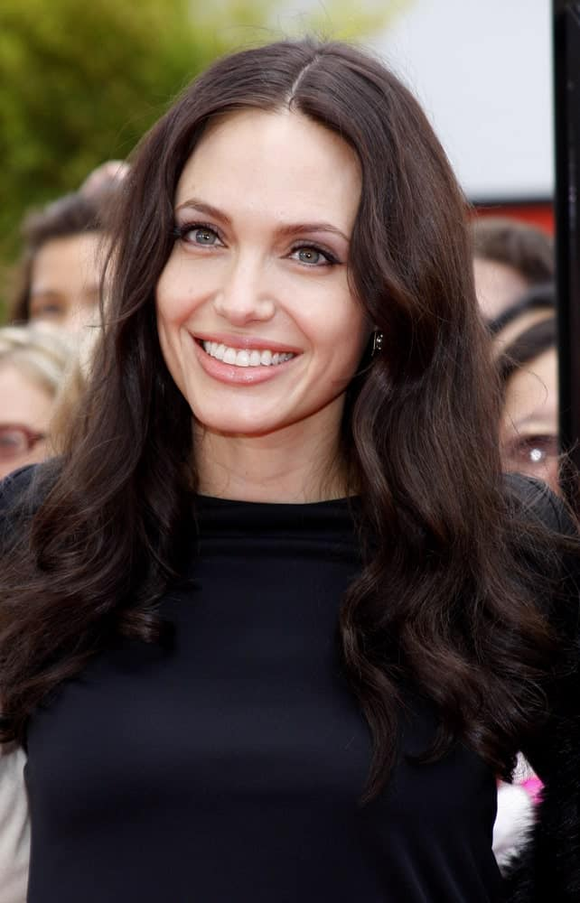 Angelina Jolie wore a center-parted wavy raven hairstyle loose on her shoulders at the Los Angeles Premiere of