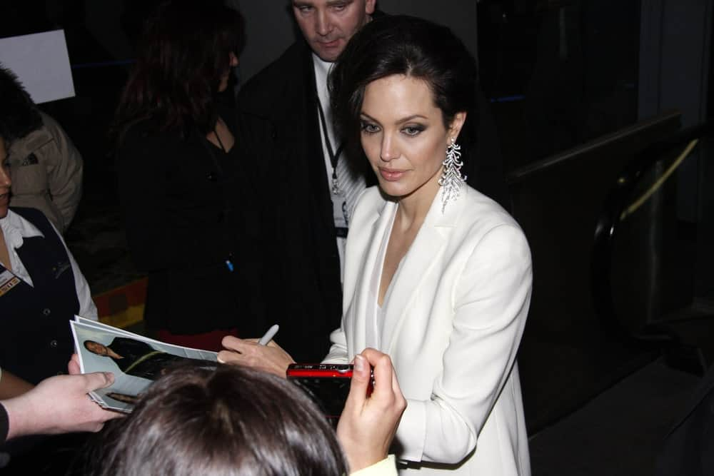 Angelina Jolie was quite fashionable in her white elegant outfit and side-swept half up tousled hairstyle to emphasize her earrings at the German premiere of The Curious Case of Benjamin Button at the Sony Center CineStar on January 19 2009 in Berlin.
