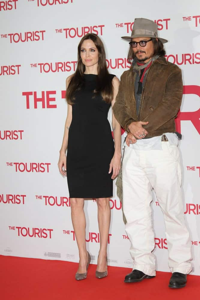 Angelina Jolie and Johnny Depp attended the Photocall of 'The Tourist' at the Hotel Adlon on December 14, 2010 in Berlin, Germany. Jolie wore a simple short black dress to go with her long and straight brunette hairstyle.