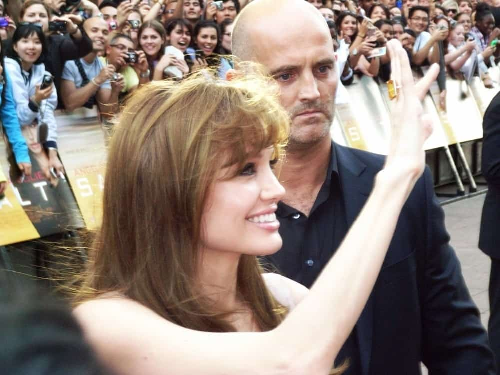 Angelina Jolie greeted her many fans with a brilliant smile and a wave at the Salt Premiere August 16th, 2010 in Leicester Square London, England. She wore her hair loose and tousled in a brown hue with bangs.
