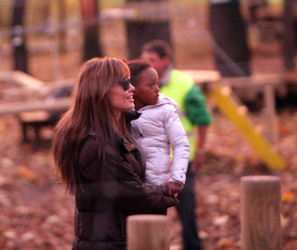 On November 5, 2010, Angelina Jolie was out and about when she took her children to a park in Budapest. She was wearing a large black winter jacket with her long and tousled loose hair with layers and bangs.