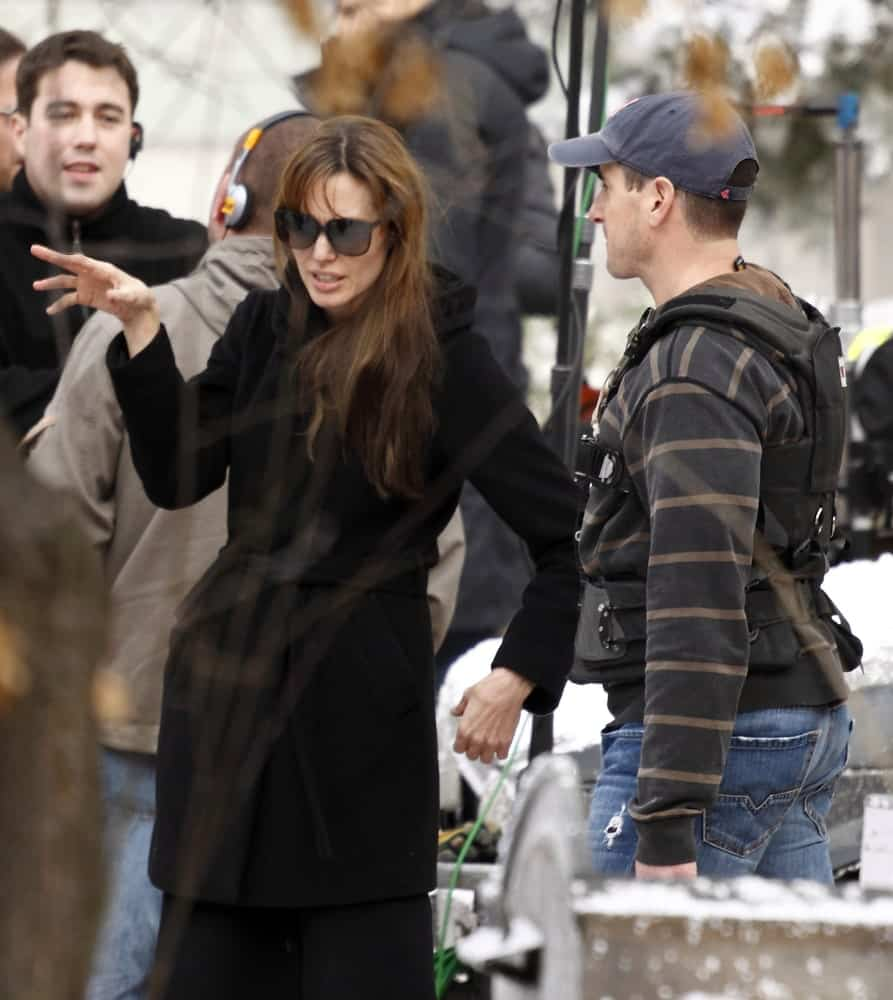 Angelina Jolie wore a large black winter coat with her loose and tousled hairstyle that has bangs and highlights at her movie shooting in the 9th District on November 9, 2010 in Budapest, Hungary.