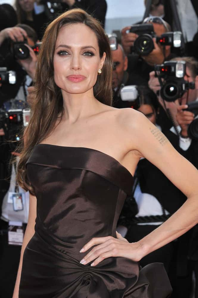 Angelina Jolie wore an elegant black silky dress to pair with her long side-swept loose and tousled layered hairstyle at the gala premiere of Brad Pitt's new movie