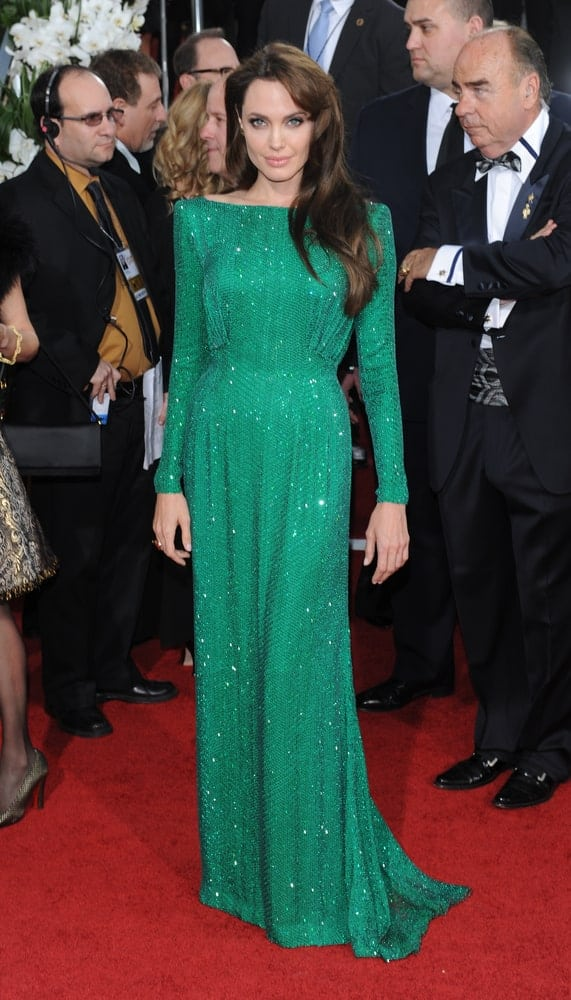 Angelina Jolie attended the 68th Annual Golden Globe Awards on January 16, 2011 in Beverly Hills, CA wearing an elegant shiny green dress to match with her side-swept long wavy dark brown hairstyle with layers.