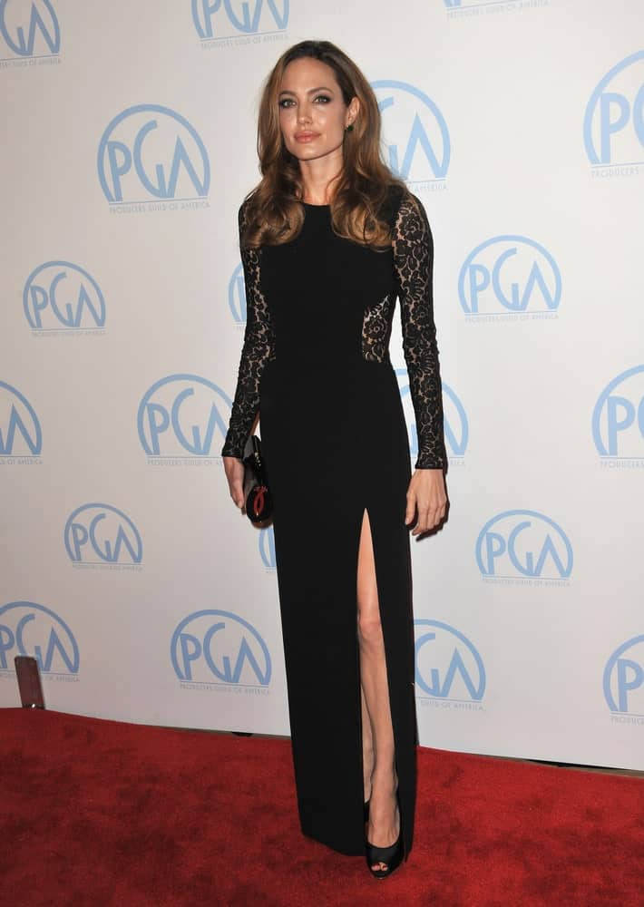 Angelina Jolie's elegant black dress with floral details at the arms went quite well with her long and loose brunette hairstyle with curls and layers at the tips for a vintage look at the 23rd Annual Producers Guild Awards at the Beverly Hilton Hotel on January 21, 2012.