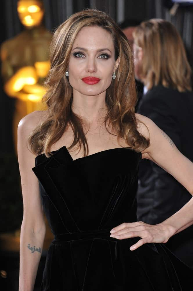 Angelina Jolie wore a black velvet dress that totally went well with her bold red lips and side-swept long tousled hairstyle with a brown tone and curls at the tips at the 84th Annual Academy Awards at the Hollywood & Highland Theatre, Hollywood on February 26, 2012.