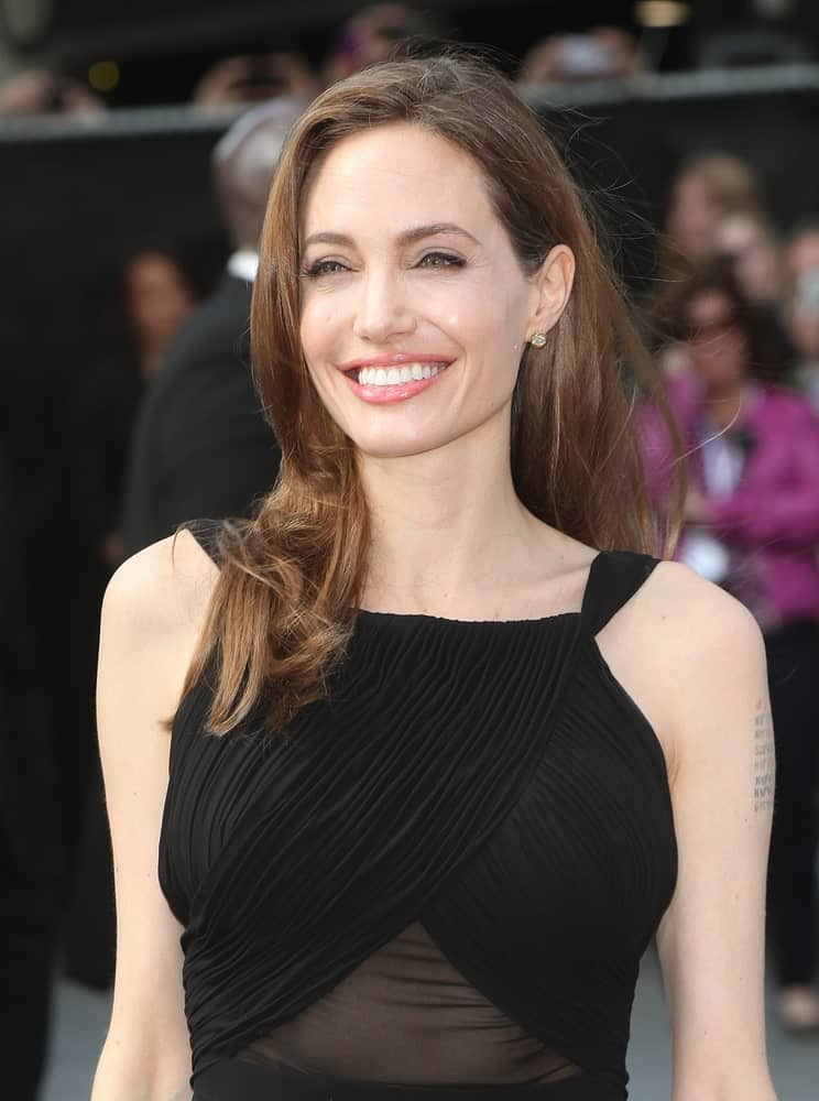 On February 6, 2013, Angelina Jolie wowed everyone with her brilliant smile, sheer black dress and her loose, long tousled brunette hair when she arrived at the World War Z World Premiere, at Empire Leicester Square, London.