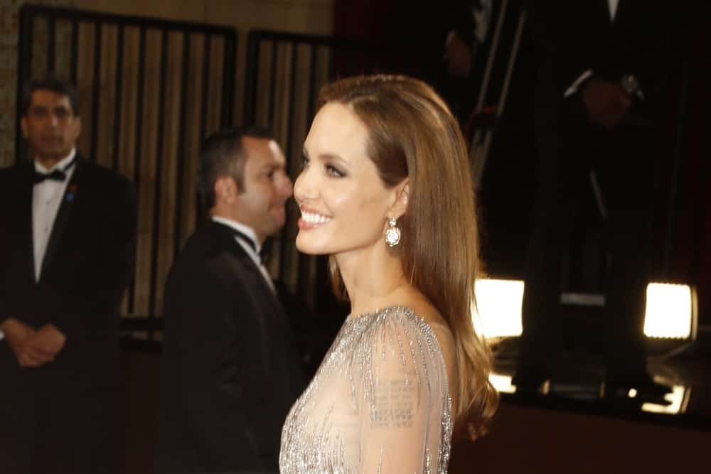Angelina Jolie flashed her beautiful smile at the 86th Annual Academy Awards at Hollywood & Highland Center on March 2, 2014 in Los Angeles, California. She wore a lovely sheer dress that she paired with her long and loose brunette hairstyle tucked behind her ear.
