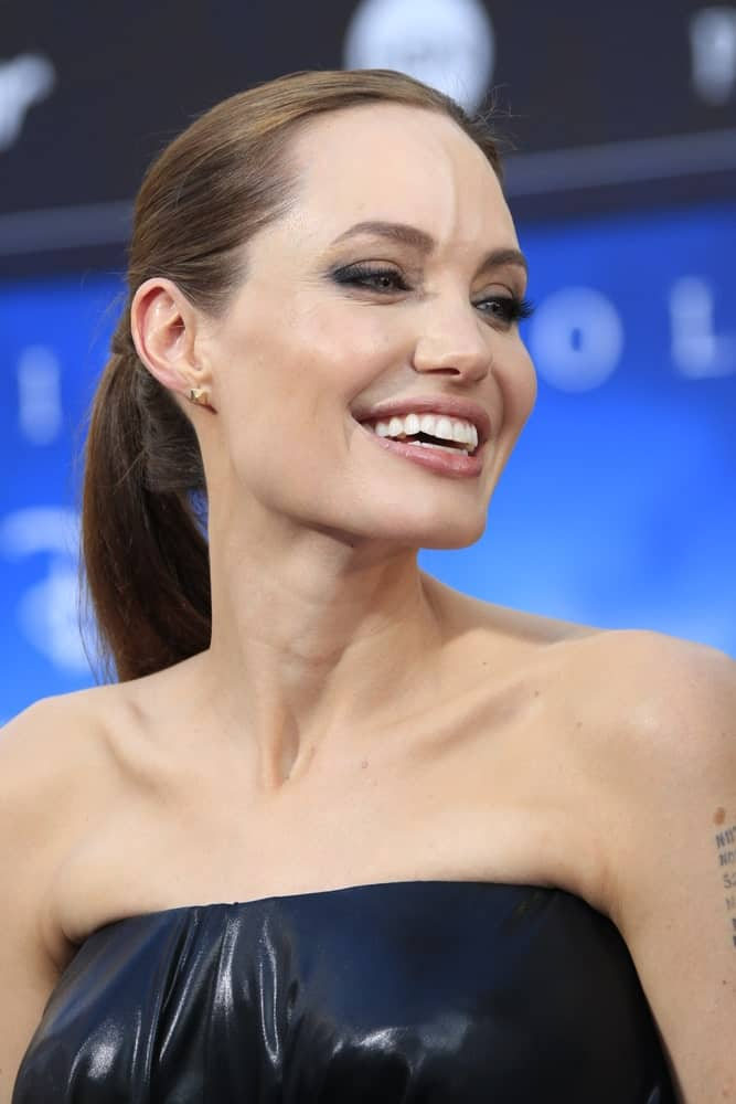 Angelina Jolie wore a strapless black leather outfit with her simple yet lovely ponytail with a slick finish at the