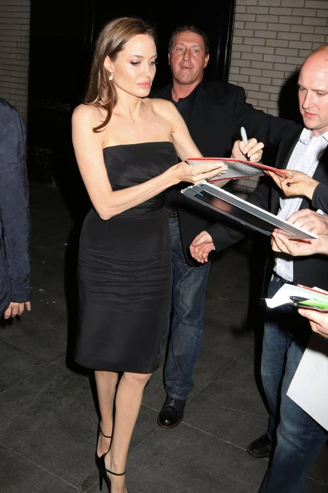 Angelina Jolie was seen signing some autographs for the fans on May 12, 2014 in the streets of New York City. She was quite charming in her black dress and long side-swept hairstyle with a silky straight finish and a dark brown tone.