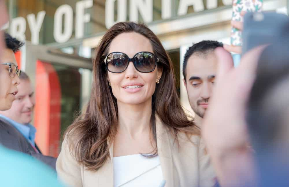 Angelina Jolie signed some autograph for the fans after the Women in the World Canada Summit during the 2017 Toronto International Film Festival on September 11, 2017 in Toronto, Canada. She wore a pair of cool sunglasses to go with her loose and tousled straight hairstyle.