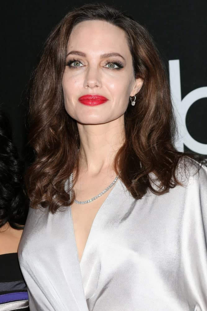 Angelina Jolie emphasized her sexy bold red lips with an elegant silvery dress and medium-length wavy hairstyle with subtle highlights at the 2017 Hollywood Film Awards at Tao on November 5, 2017 in Los Angeles, CA.