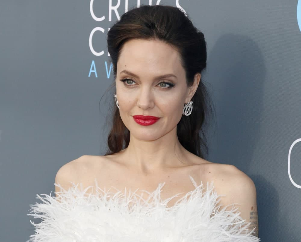 Angelina Jolie wore a stunning white strapless dress with feathers to pair with her lovely half up hairstyle at the 23rd Annual Critics' Choice Awards held at the Barker Hangar in Santa Monica, USA on January 11, 2018.