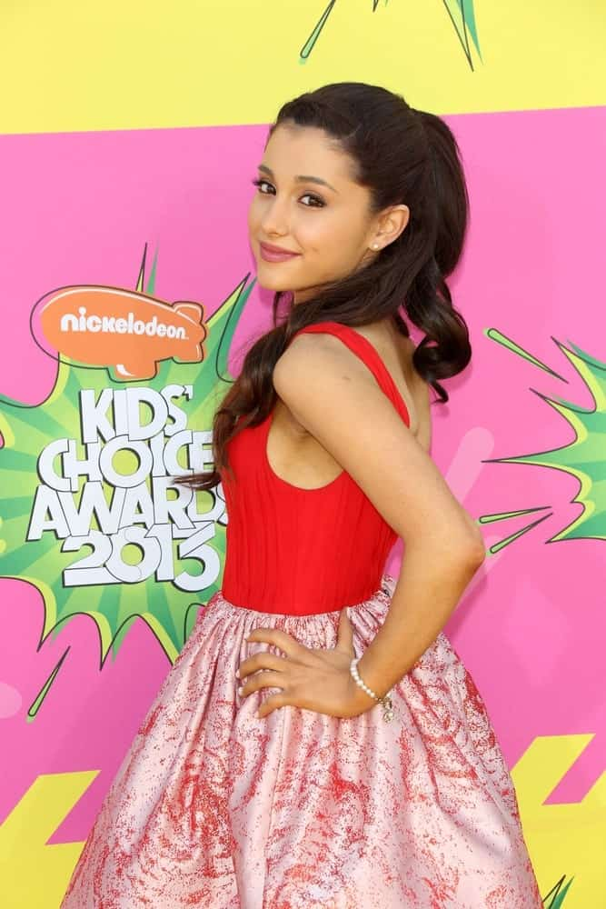 Ariana Grande strikes a pose with her long, brown waves that are styled in a half updo during the 26th Annual Kids' Choice Awards on March 23, 2013.
