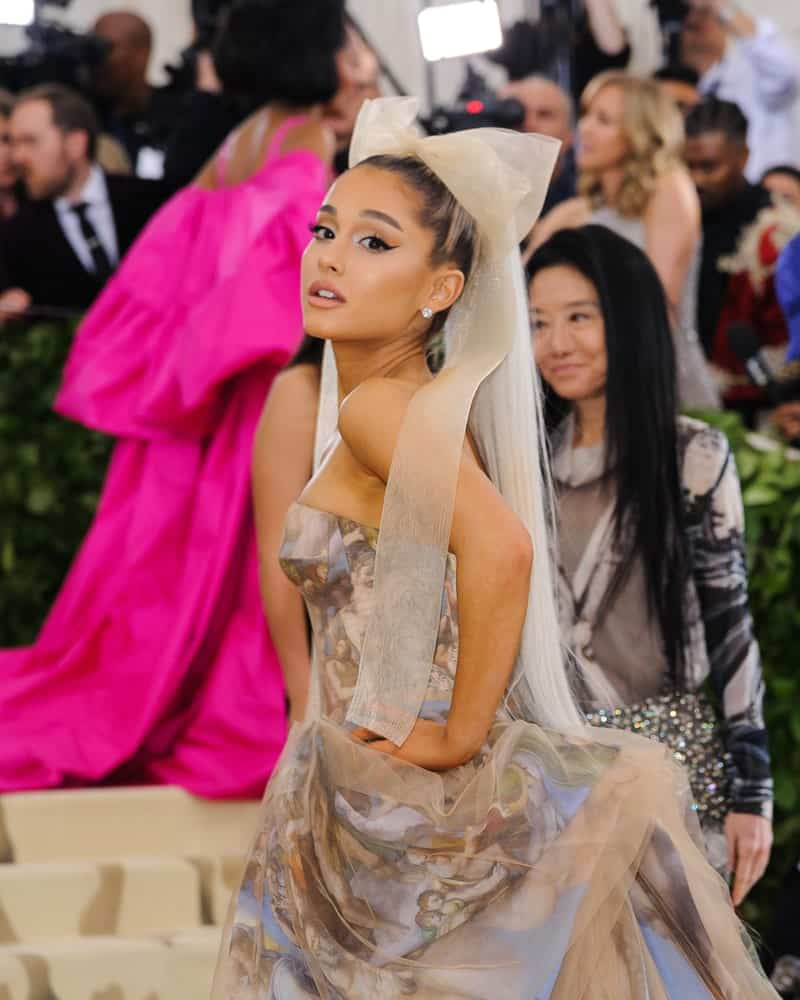 Ariana Grande complements her ponytail hairstyle with a dramatic long organza bow during the 2018 Metropolitan Museum of Art Costume Institute Benefit Gala on May 7, 2018. She finished the look with a glamorous floral dress and stud earrings.