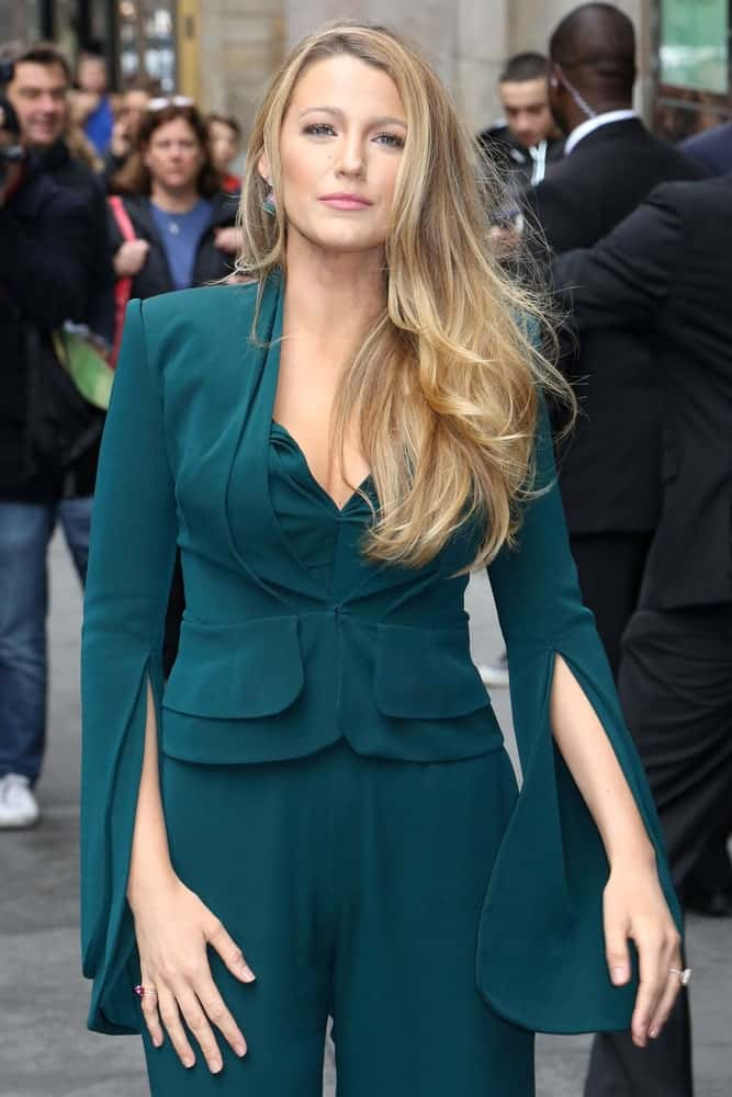 Blake Lively was seen wearing an emerald green pantsuit back in April 21, 2017 walking the streets of New York City. Her outfit was paired with a long and wavy side-swept sandy blond hairstyle.