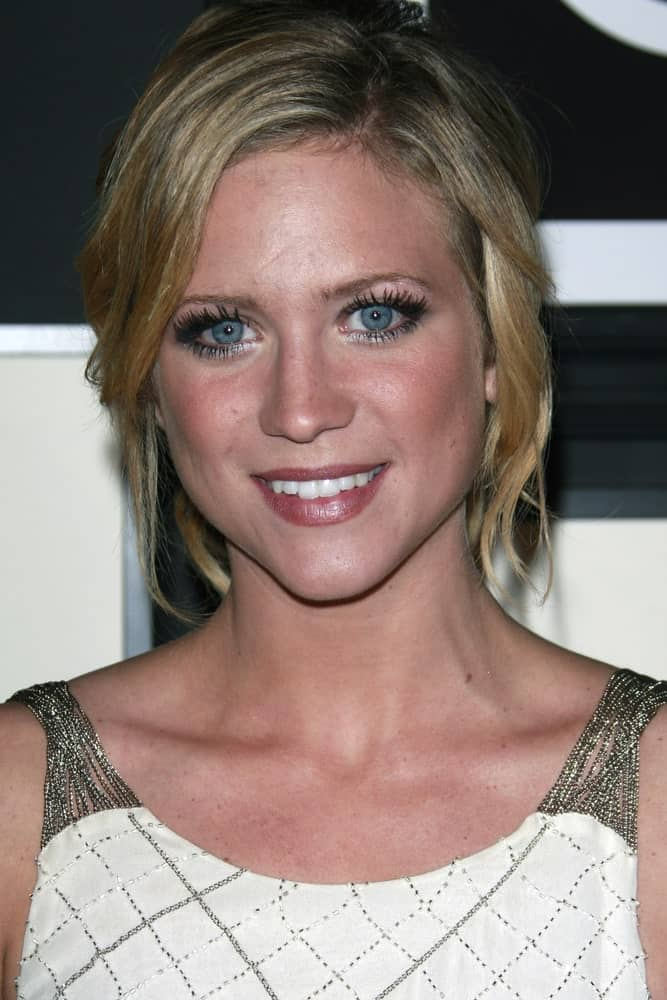 Brittany Snow was at the Target & Converse Party at the Lot on June 1, 2008 in Los Angeles, California. she wore a casual white dress that she paired with a messy blonde bun hairstyle that has loose bangs and tendrils.