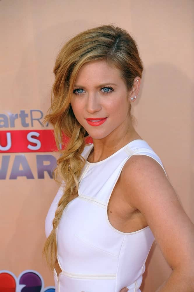 On March 29, 2015, Brittany Snow attended the 2015 iHeart Radio Music Awards at the Shrine Auditorium. She paired her white dress with a long, layered and highlighted side-swept blonde hairstyle with fishtail braids.