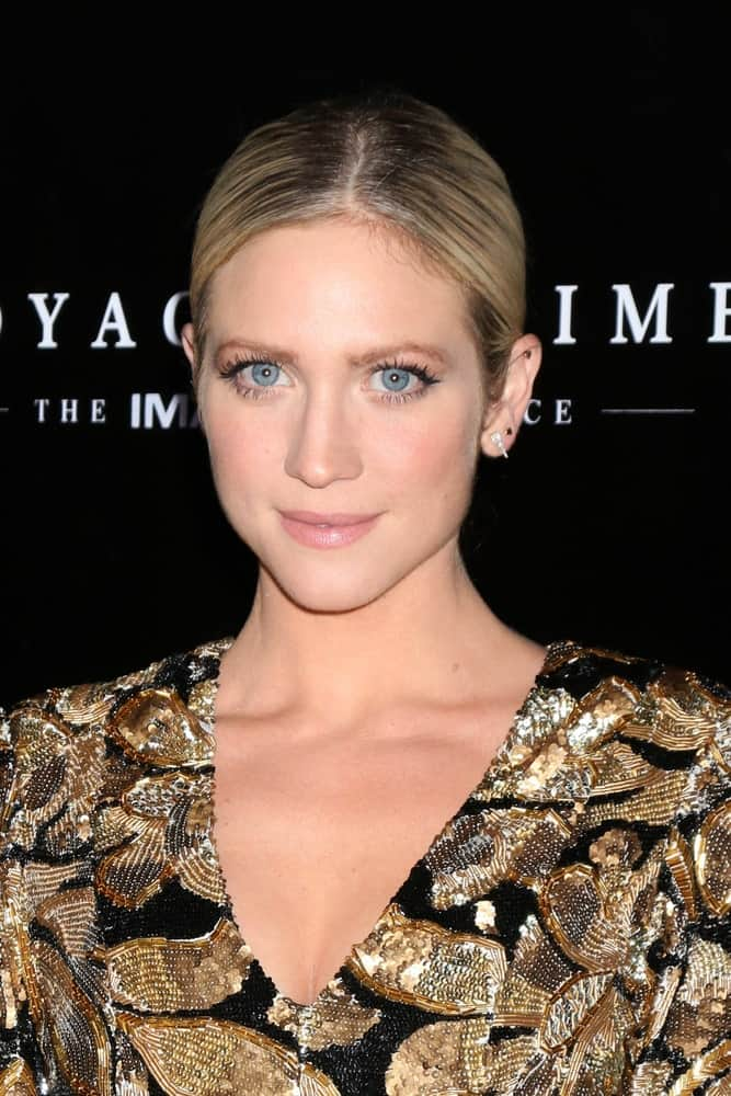 She wore a gold and black patterned dress that went well with her slick highlighted blond ponytail hairstyle.Brittany Snow at the