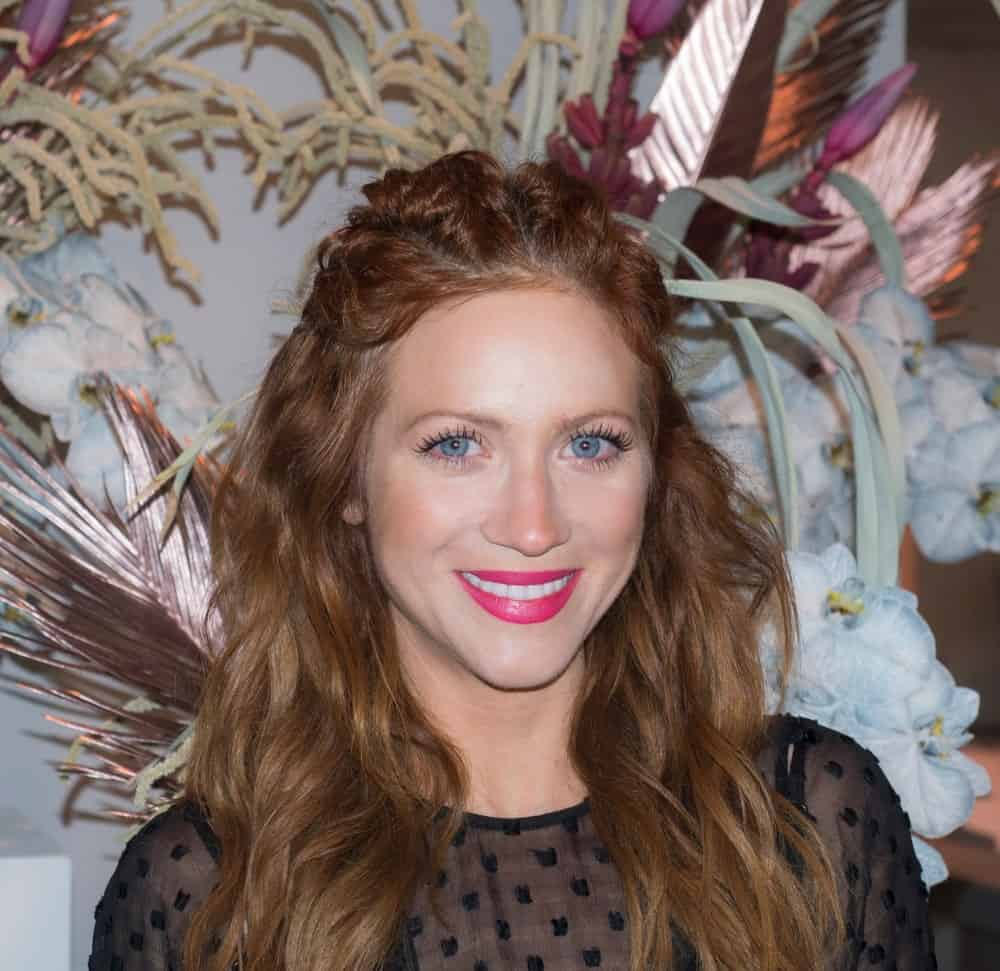 On February 10, 2018, actress Brittany Snow attended the Alice McCall Fall/Winter 2018 runway show during New York Fashion Week at Industria, Manhattan. She wore a black sheer dress with her curly and loose tousled long brunette half-up hairstyle incorporated with braids.