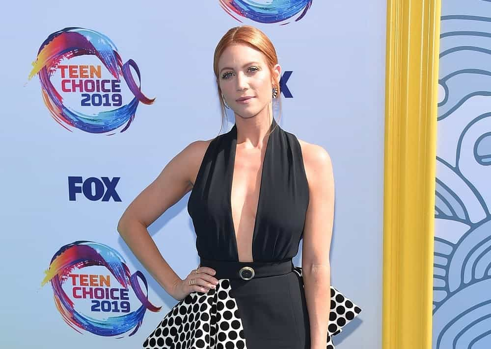 Brittany Snow was at the 2019 Teen Choice Awards on August 11, 2019 in Hermosa Beach, CA. She wore a lovely black dress with her red hair in a bun hairstyle that has loose tendrils.