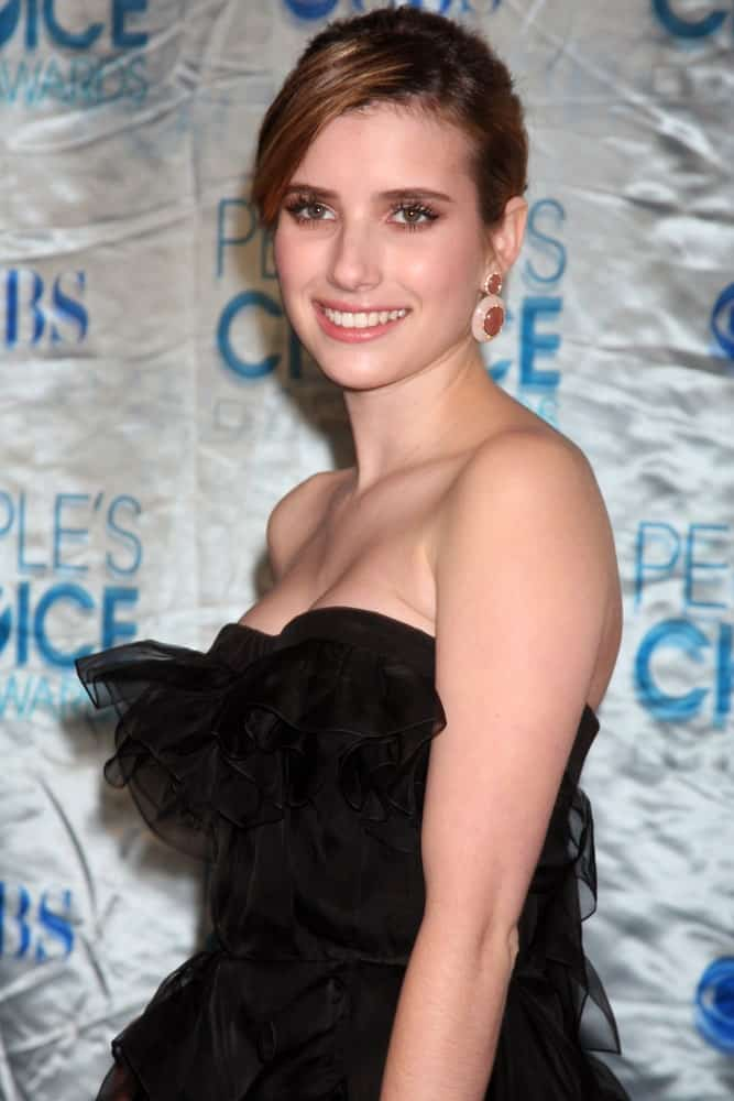 Emma Roberts was at the 2011 People's Choice Awards at Nokia Theater at LA Live on January 5, 2011 in Los Angeles, CA. She wore a strapless black dress with her brunette bun hairstyle with long side-swept bangs.