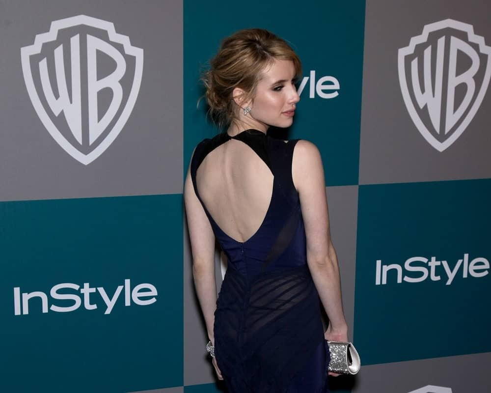 Emma Roberts attended the Golden Globes 2012 After Party: WB / In Style on January 15, 2012 in Beverly Hills, CA. She paired her stunning dress with a brunette low bun hairstyle with long side-swept bangs.