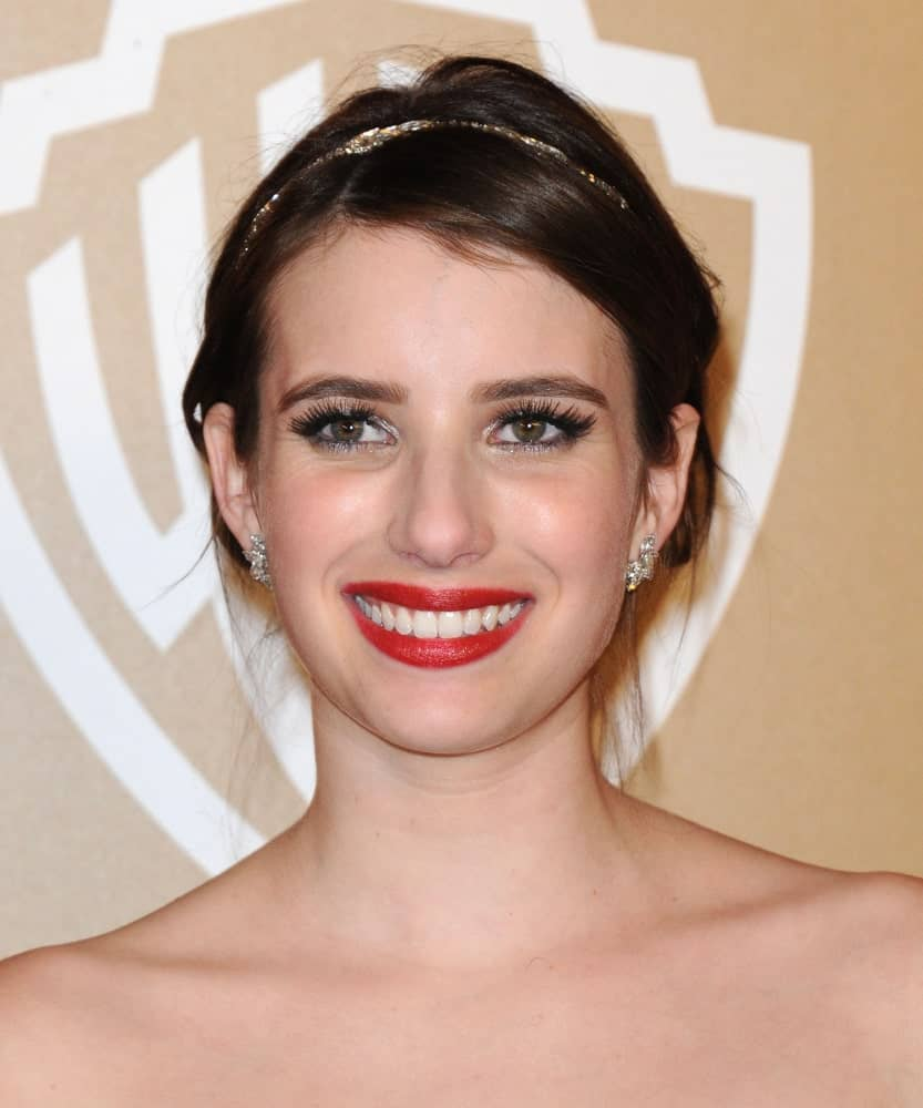 Emma Roberts was at the WB/In Style Golden Globe Party on January 13, 2013 in Hollywood, CA. She wore a strapless dress with her messy dark bun hairstyle with a golden headband.