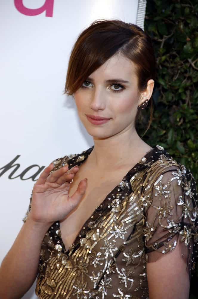 Emma Roberts attended the 21st Annual Elton John AIDS Foundation Academy Awards Viewing Party held at the West Hollywood Park in Los Angeles on February 24, 2013. She paired her elegant sheer dress with a brunette bun hairstyle that has long side-swept bangs.