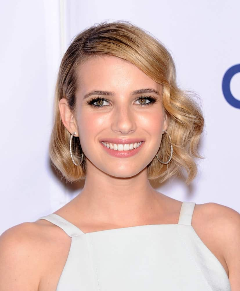 Emma Roberts was at the Paleyfest 2014: American Horror Story COVEN on March 28, 2014 in Hollywood, CA. She wore a white dress that she topped with a chin-length tousled blonde hairstyle with vintage curls and side-swept bangs.