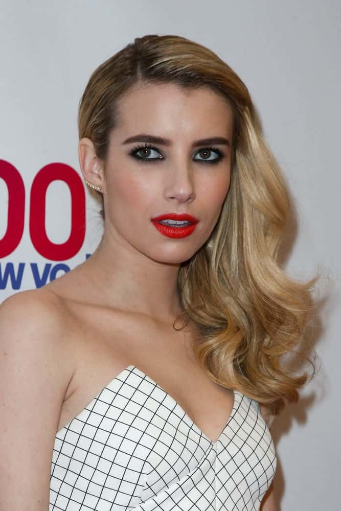Actress Emma Roberts attended Z100's Jingle Ball 2014 at Madison Square Garden on December 12, 2014 in New York City. She wore a white patterned strapless outfit with her side-swept and highlighted wavy blonde hairstyle.