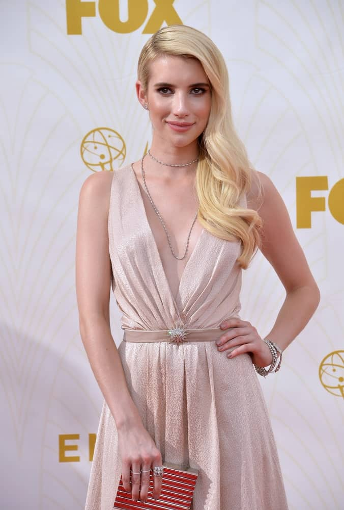 On September 20, 2015, Emma Roberts was at the 67th Primetime Emmy Awards at the Microsoft Theatre LA Live. She came wearing a beige dress to pair with her long sandy blonde side-swept hairstyle with waves.