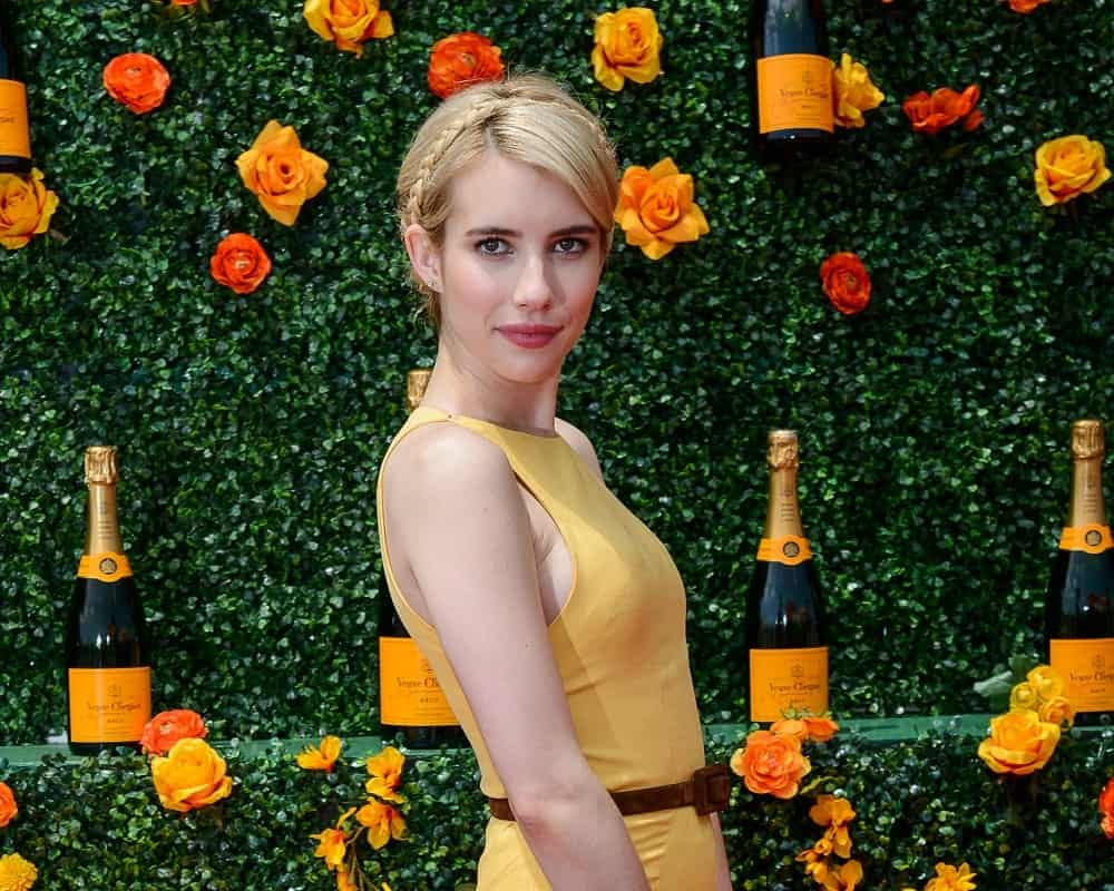 On May 30, 2015, Emma Roberts attended the 8th Annual Veuve Clicquot Polo Classic in Liberty State Park, New Jersey City. She paired her charming yellow dress with a blonde bun hairstyle incorporated with braids.