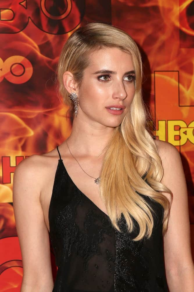 Emma Roberts was at the HBO Primetime Emmy Awards After-Party at the Pacific Design Center on September 20, 2015 in West Hollywood, CA. SHe wore a stunning black dress with her side-swept long and wavy blonde hairstyle with layers.