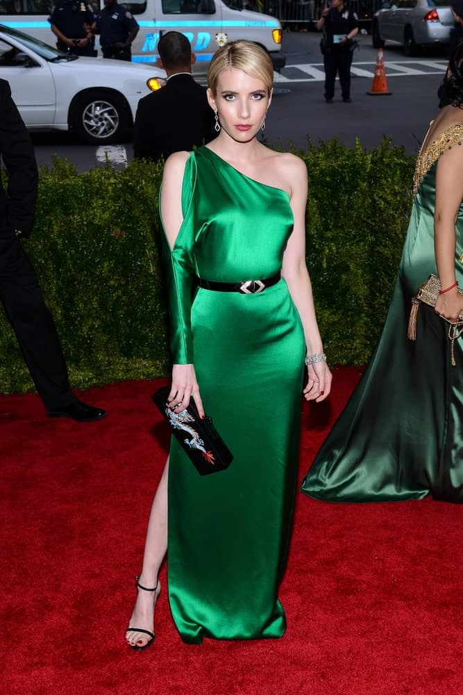 On May 04, 2015, Emma Roberts attended 'China: Through The Looking Glass' Costume Institute Gala, held at the Metropolitan Museum of Art in New York City, New York. She wore an elegant green silk dress with her sandy-blonde bun hairstyle with a slick finish.