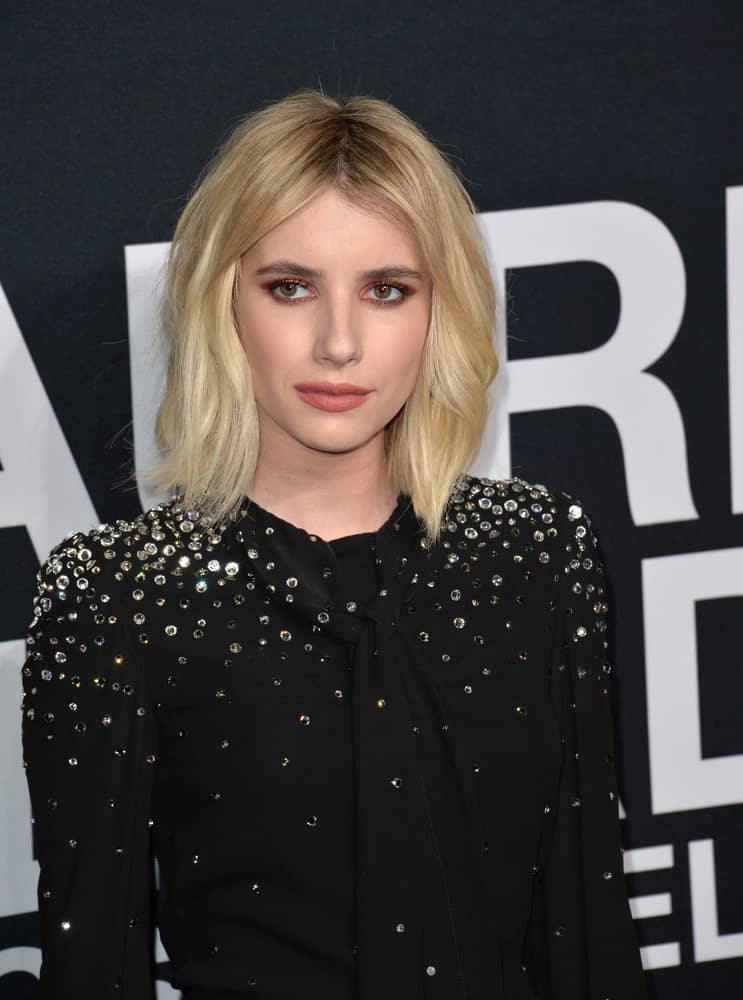 On February 10, 2016, actress Emma Roberts was at the Saint Laurent at the Palladium fashion show at the Hollywood Palladium. She wore a sparkly black dress with her shoulder-length tousled blonde bob hairstyle with layers.