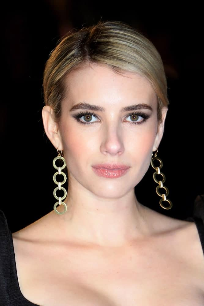 On February 18, 2018, Emma Roberts attended the EE British Academy Film Awards (BAFTAs) held at the Royal Albert Hall in London, UK. She wore an elegant black dress with her slick side-parted hairstyle with highlights.