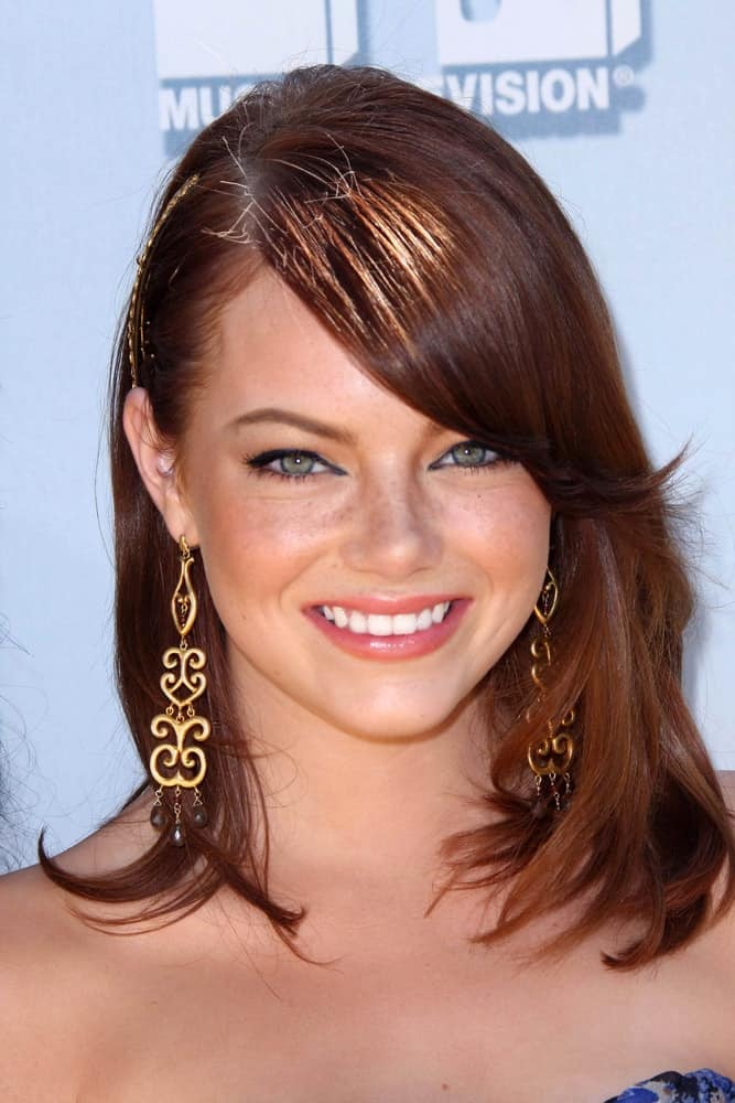 On June 1, 2008, Emma Stone flashed her brilliant smile with her layered side-swept hairstyle at the 2008 MTV Movie Awards at the Gibson Amphitheatre in Universal City, CA.