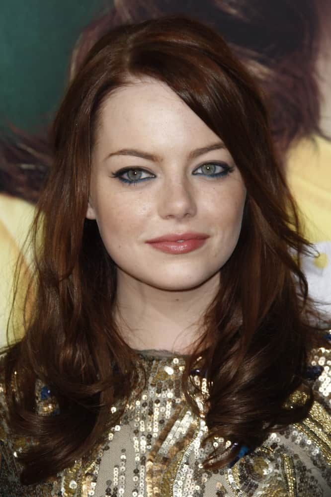 Emma Stone attended the premiere of 'Easy A' at the Grauman's Chinese Theater in Los Angeles, California on September 13, 2010. She wore a lovely gold sequined dress to pair with her layered dark red hair that has tight curls at the tips.