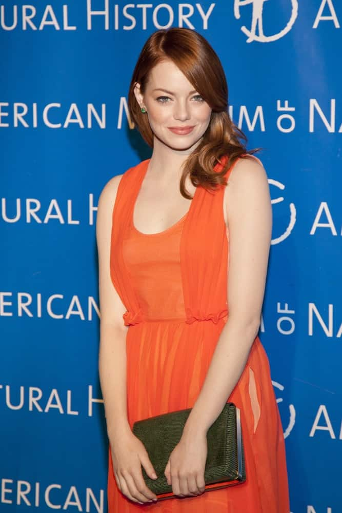 Emma Stone looked quite lovely in her bright orange dress, bold lips and silky straight side-swept red hairstyle with long bangs when she attended the American Museum of Natural History's 2011 Gala on November 10, 2011 in New York City, NY.