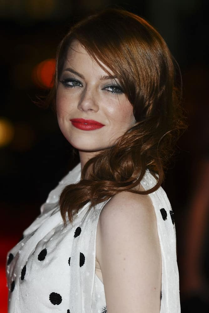 On May 10, 2011, Emma Stone was at the premiere of 'The Help' at the Curzon Mayfair in London. She wore a lovely white polka-dotted dress that she paired with a side-swept red hairstyle with tight curls.